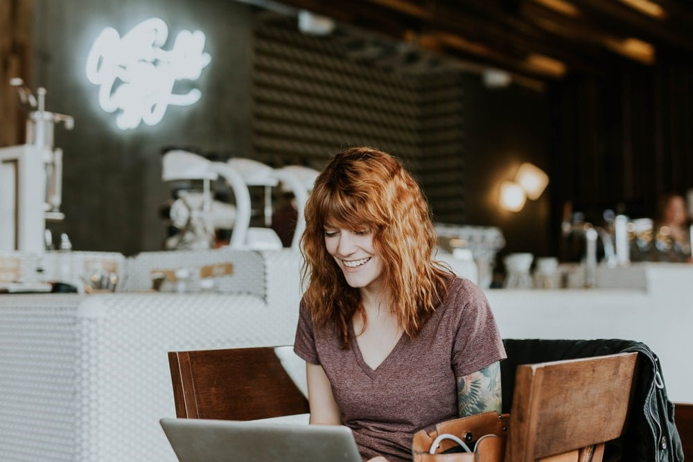 smiling woman with red hair typing on her laptop